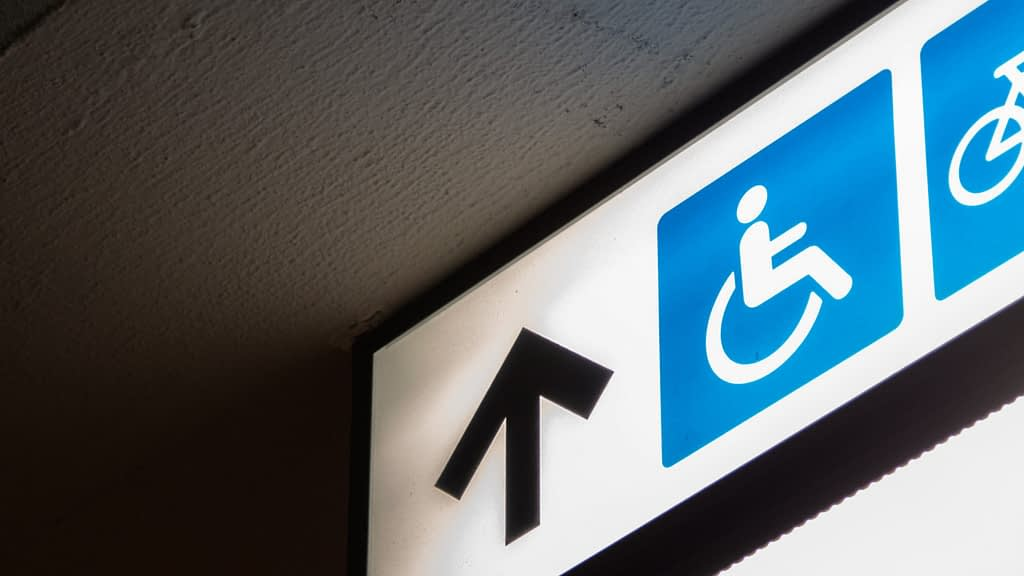 disabled sign on the ceiling with an arrow pointing upwards