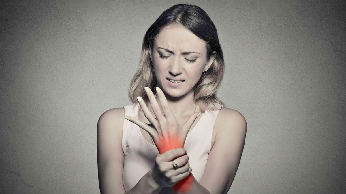 Young woman holding her wrist from joint pain using CBD oil to treat