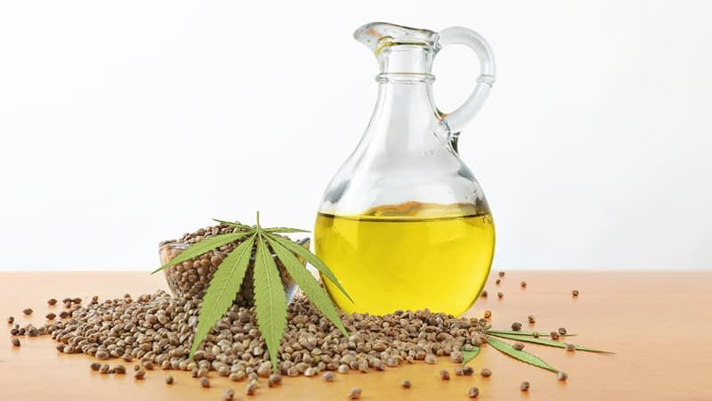 Hemp oil in glass jar and hemp seed on a table in white background